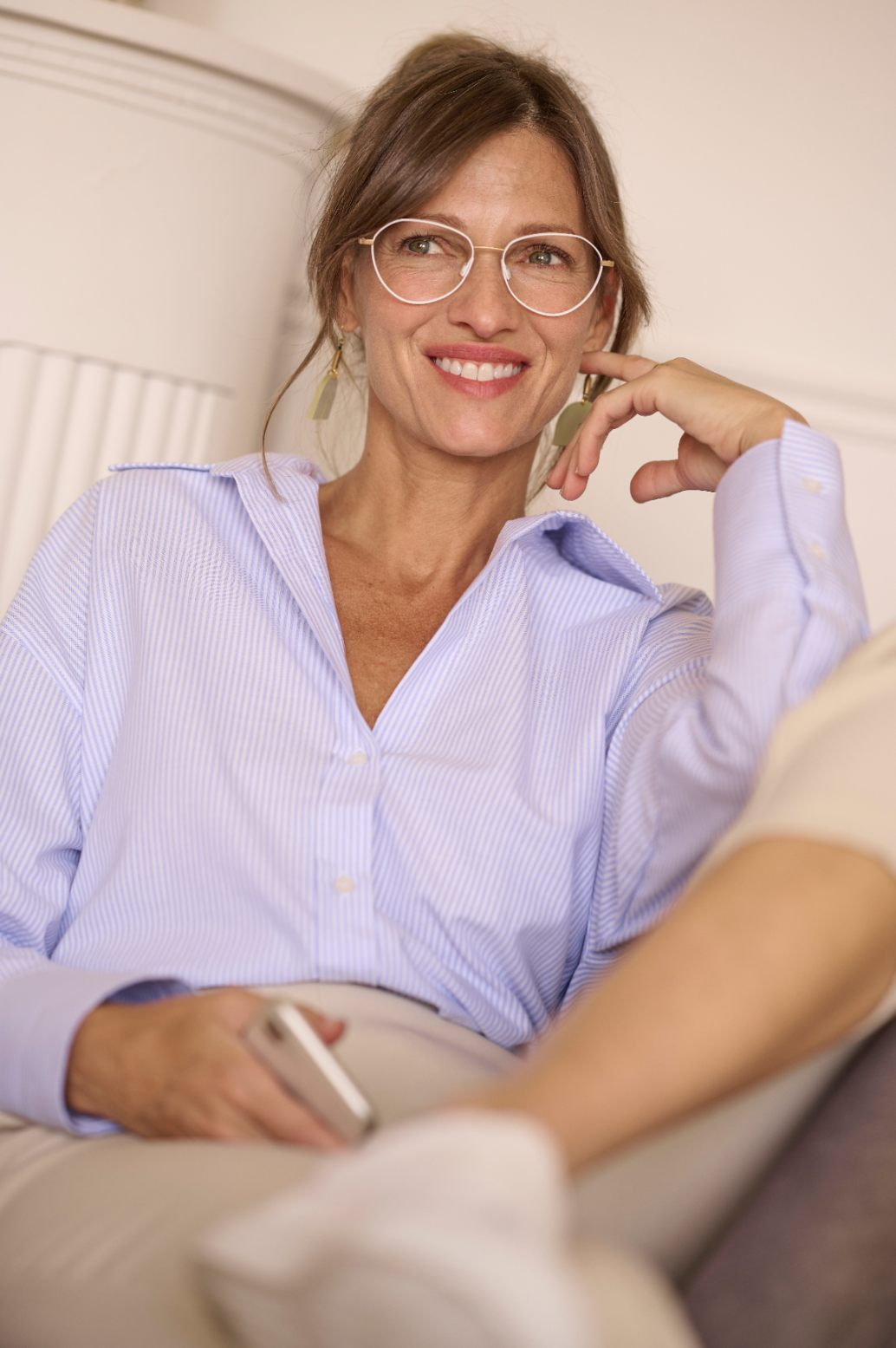 Woman wearing glasses sitting and smiling while looking away